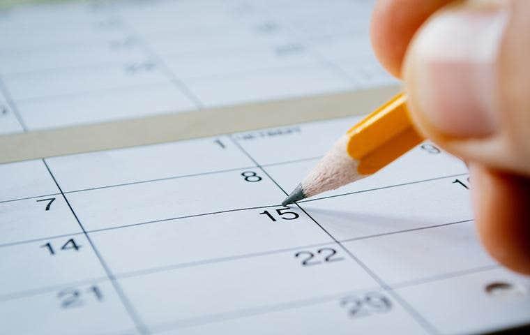person marking date on calendar