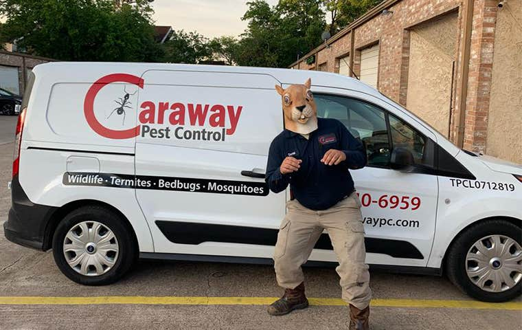 tech with a squirrel mask in front of company truck