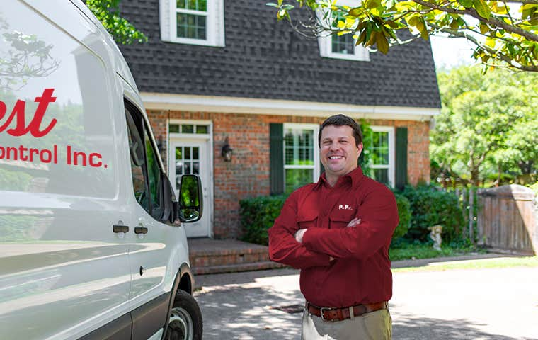 pro pest technician in front of house with company vehicle