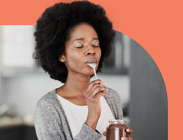Young woman savouring the taste of chocolate spread she is eating with a spoon out of the jar.
