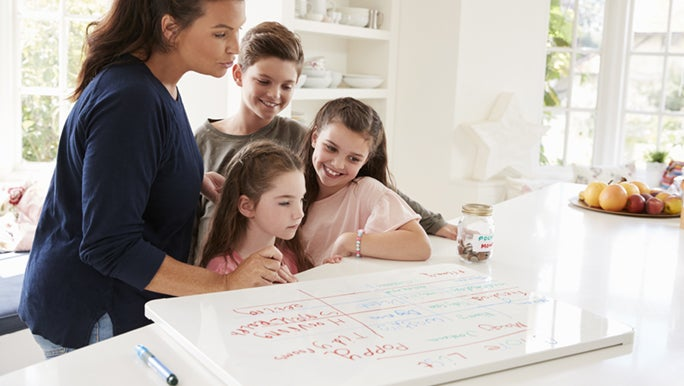 A mum shows her three primary aged kids a routine chart she has made on a whiteboard.