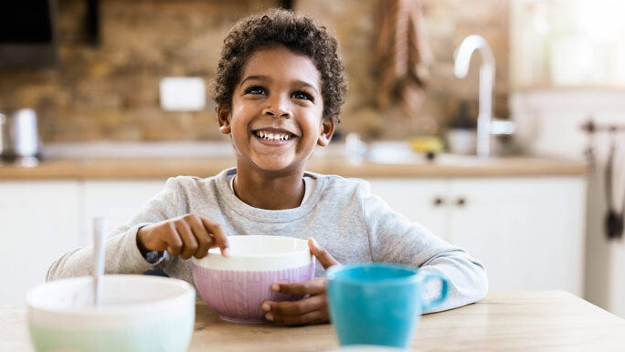 Happy, smiling boy eat a bowl of cereal at the kitchen table