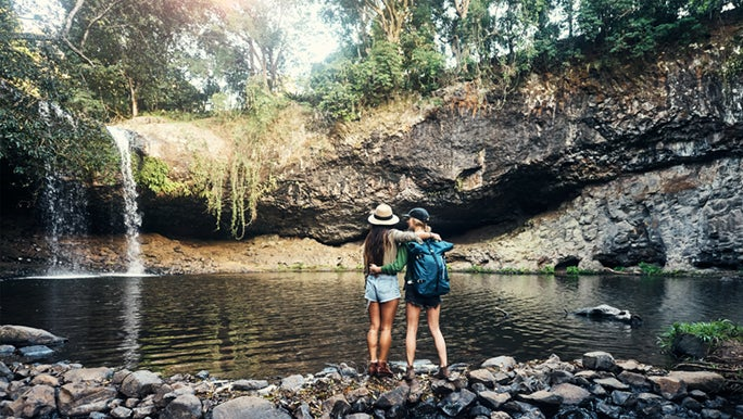 Two people are standing at a waterhole in the Australian bush, they have been hiking and have their arms around each other.