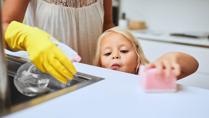 A little girl helps her mum wipe down the benchtop with a pink sponge. She is learning responsibility and building her resilience.