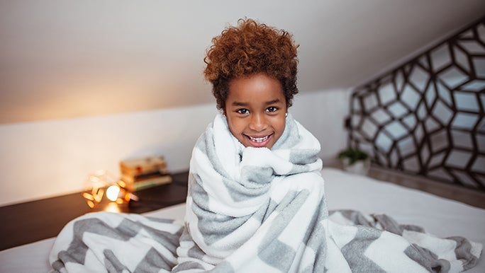 A little boy is wrapped up in a weighted blanket, he is smiling and cosy looking.