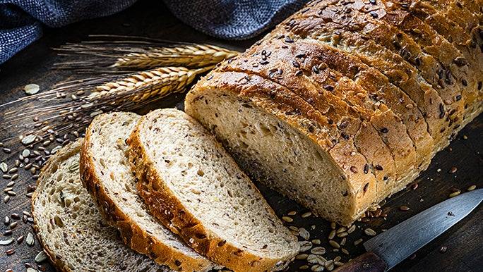 A loaf of multigrain bread, sliced on a chopping board, surrounded by grains and seeds.