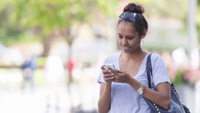A woman stops during her walking commute to reply to a text message, she is happy and may be talking to a long distance friend.