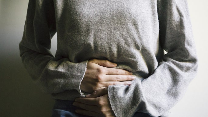A close up shot of a woman holding her stomach, she is experiencing lower back period related pain.