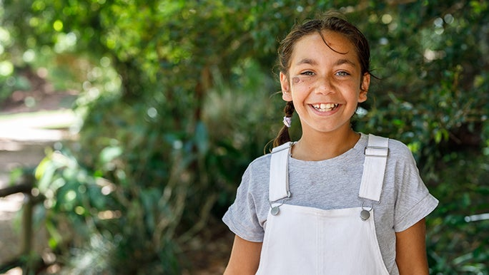 A girl is standing outside in a green, leafy environment looking happy as her parents wonder why outdoor play is important for children.