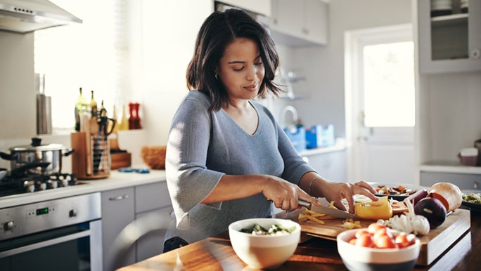 Woman in kitchen preparing vegetables for healthy hair and nails.
