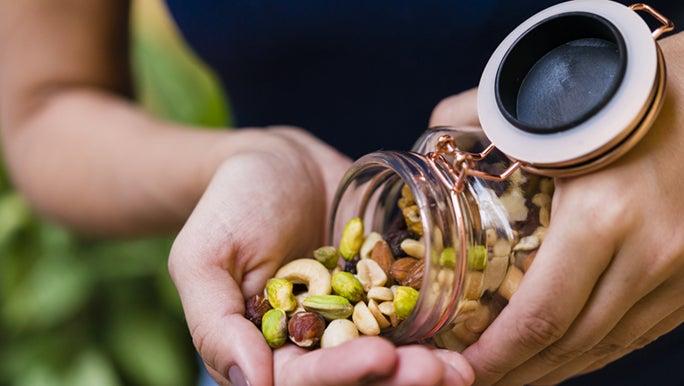 A close up shot of a jar full of mixed nuts.