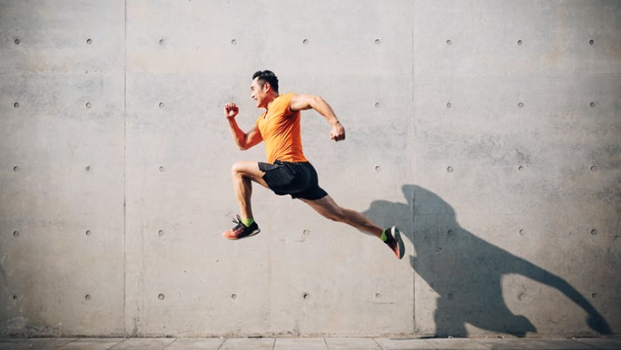 Man jumping in a running post in front of a concrete wall, he is at risk of getting a common sports knee injury.
