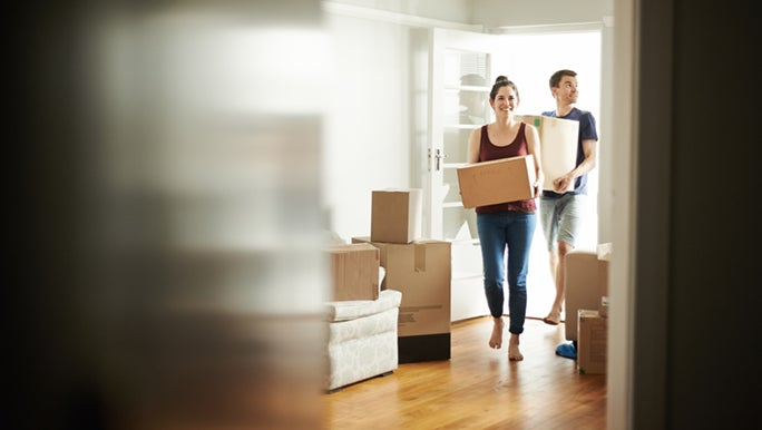 A couple carrying boxes are walking through a doorway into their new home. They followed a bunch of moving house tips and have had a stress-free move.