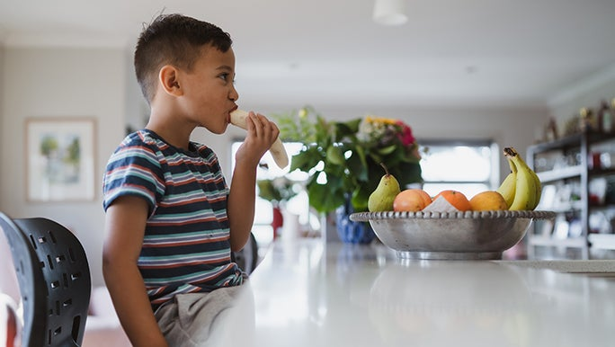 A kid is sitting at a kitchen bench eating a banana for breakfast.