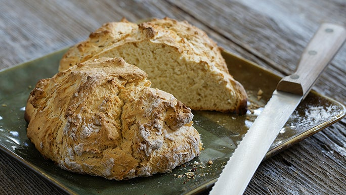 A loaf of soda bread sits on a green serving plate next to a bread knife and it could be a healthier alternative than white bread.