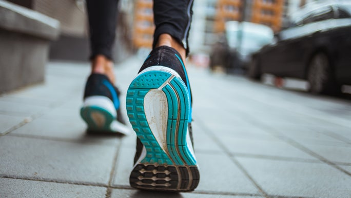 A close up of a blue sneaker in action, the owner is enjoying a morning walk through the city.