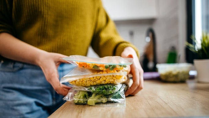 A close up of a woman storing vegetables in ziploc bags.