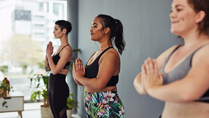 Three women stand together in an exercise or yoga studio. Their hands are in prayer pose and they all look happy.