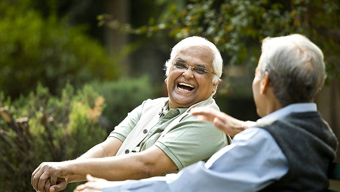 wo men sit on a park bench in the sun, chatting and laughing together.