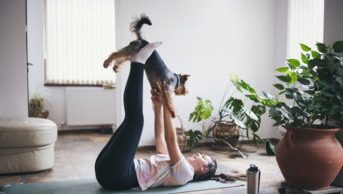 A woman is laying on her back in her apartment on a yoga mat, she is lifting her god with her feet and stretching after a long run.