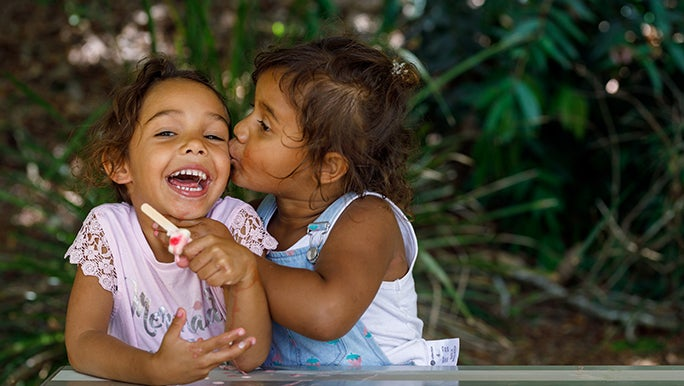 Two girls sit at a picnic table, one is kissing the other - she looks extremely grateful for the attention.
