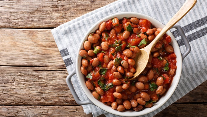 From above, a bowl of beans in tomato sauce sit on a rustic wooden table.