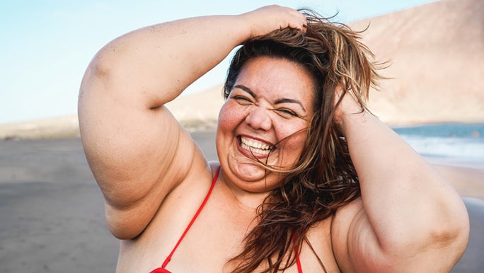 A woman in a red bikini tussles her hair on the beach, her smile is big and her eyes are closed. She knows how to feel good about herself.