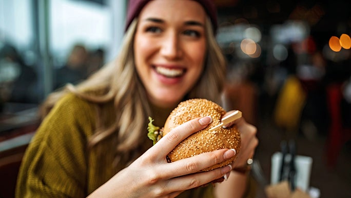 A woman is at a restaurant about to eat a hamburger roll and is wondering how a gluten-free diet impacts the immune system