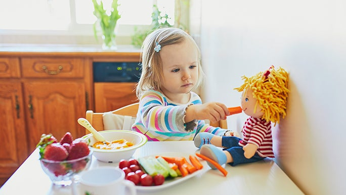 A toddler feeds a rag doll a carrot. She is sitting at a table that is packed with veggies.