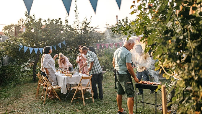 A family gathers in a leafy backyard for a BBQ. There are blue flag garlands strung around and the cook wears an apron.