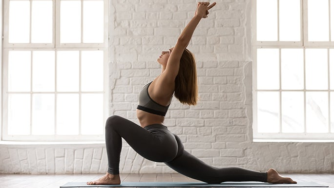 A woman is doing the yoga pose warrior one, her left knee is out in a deep bend and her right leg is stretched far behind her. Both arms are in the air.