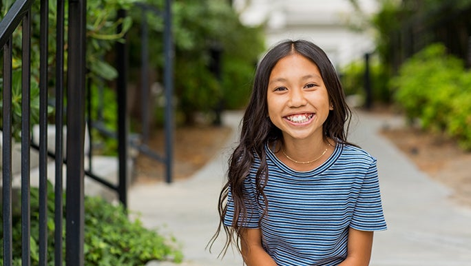 A teenage girl sits on some outside steps and smiles at the camera.