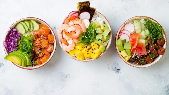 Three protein rich poke bowls with salmon, prawns, tuna, rice and fresh vegetables