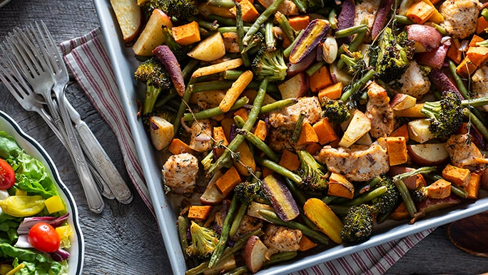 Flatlay of a chicken and vegetable sheet bake promoting the benefits of organic food.