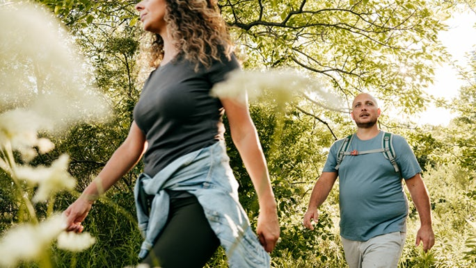 A man and woman walk through the bush, they are prioritising fitness as they age healthily.