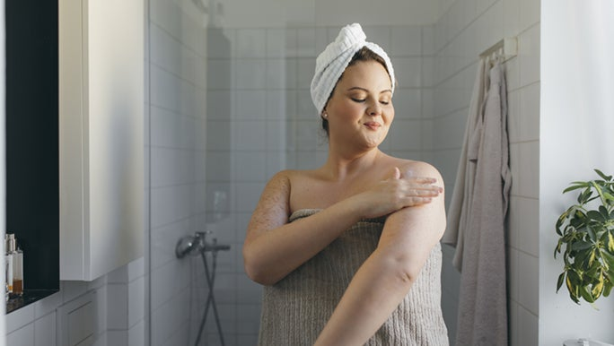 A lady dressed in a towel is applying moisturiser after her shower. Hopefully she is exploring how to boost her self worth.