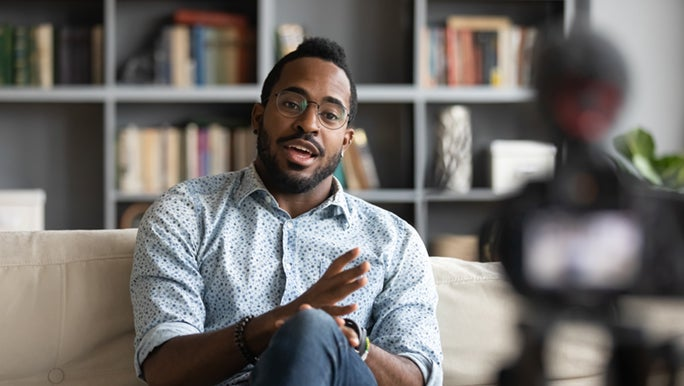 A life coach sits on the couch, he is mid sentence talking to a camera. He is wearing glasses and looks energetic and uplifting.