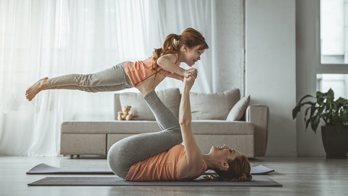 Mum is laying on the floor of her lounge room on a yoga mat. She is lifting her child in the air with her feet.