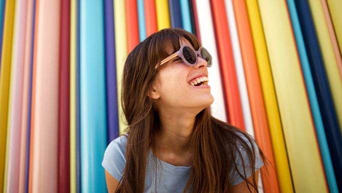 A woman smiles in front of a colourful background. She is outside decluttering her mind during her lunch break.