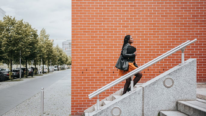 A woman is choosing to take the stairs so she can get her daily exercise in. There is an orange brick wall behind her and she looks to be in office wear.