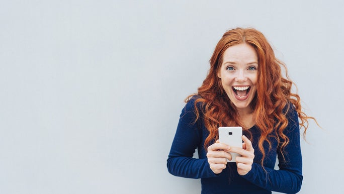 Vivacious young woman laughing at a good joke as she stands against a white wall with copy space holding a mobile