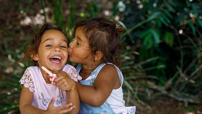 Two little girls sit at a metal picnic table, one is eating an ice cream and smiling as the other kisses her cheek.