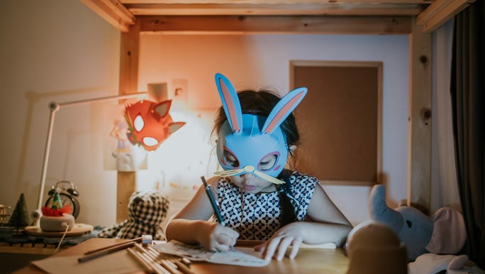 Young girl wearing a rabbit mask doing her homework