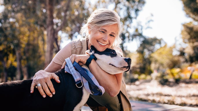 A lady is cuddling a dog in a park, they are meeting their minimum exercise requirements by going for a walk outdoors.