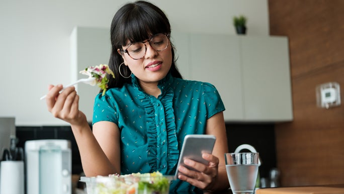 Young woman eating a salad and checking her phone