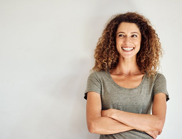 Happy and confident woman standing against a grey wall