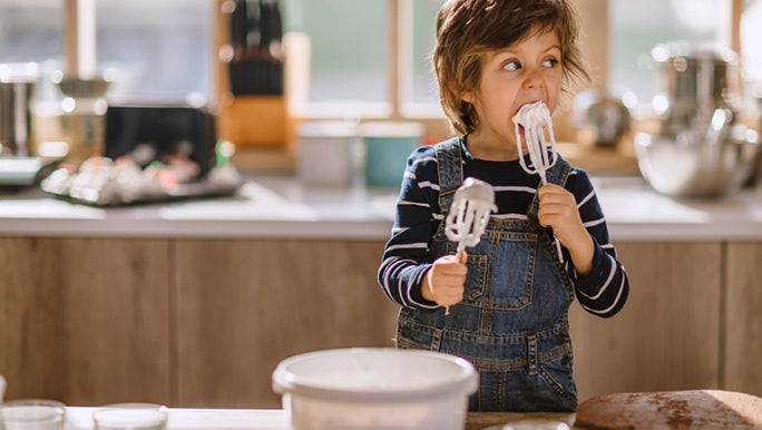 Child standing at a kitchen bench licking icing off beaters. His parents are about to experience the effects of too much sugar.