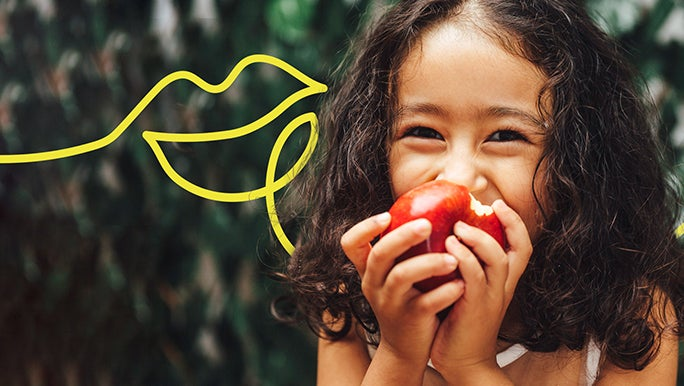 Happy girl smiling and eating a red apple
