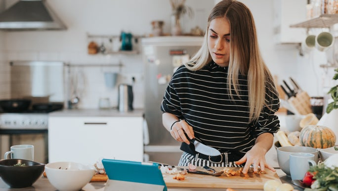 Teenage girl following a recipe on her ipad to make a healthy meal
