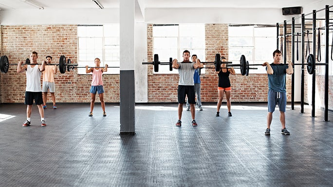 Seven people lifting barbell weights in a fitness class. Heavy lifting is the best way to build muscle.